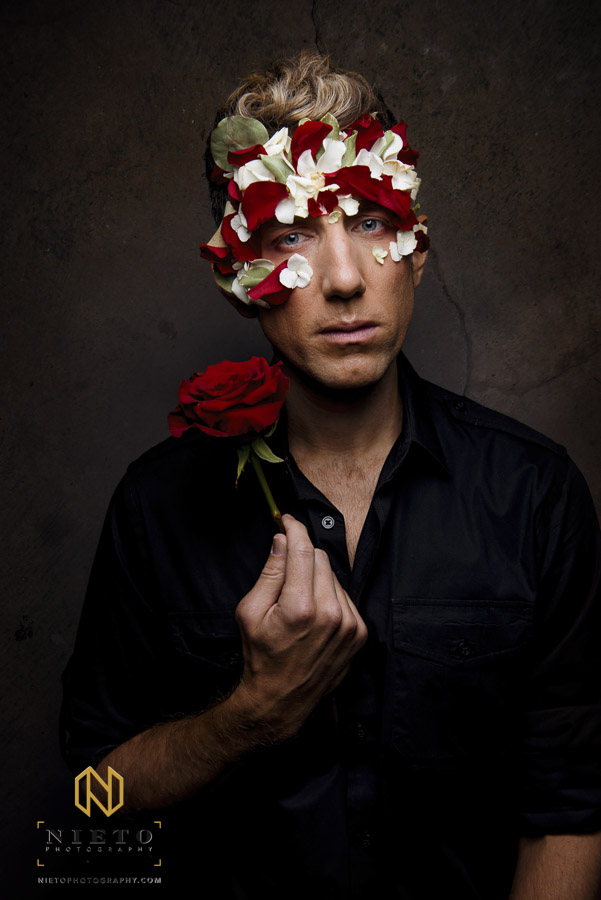 Male model with flower mask and rose in his hand