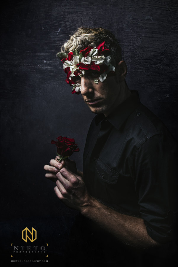 Male model with rose in his hand and flower mask against dark wall