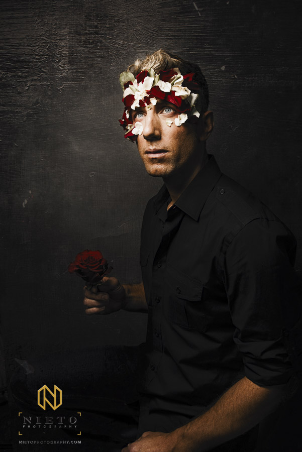 male model holding a rose with petals all around his face