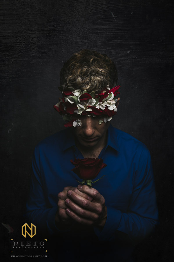 Male model with flower mask and rose in hand while wearing a blue shirt