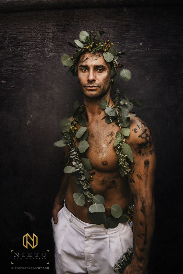 Shirtless male model wrapped in greenery and covered in black and gold make up