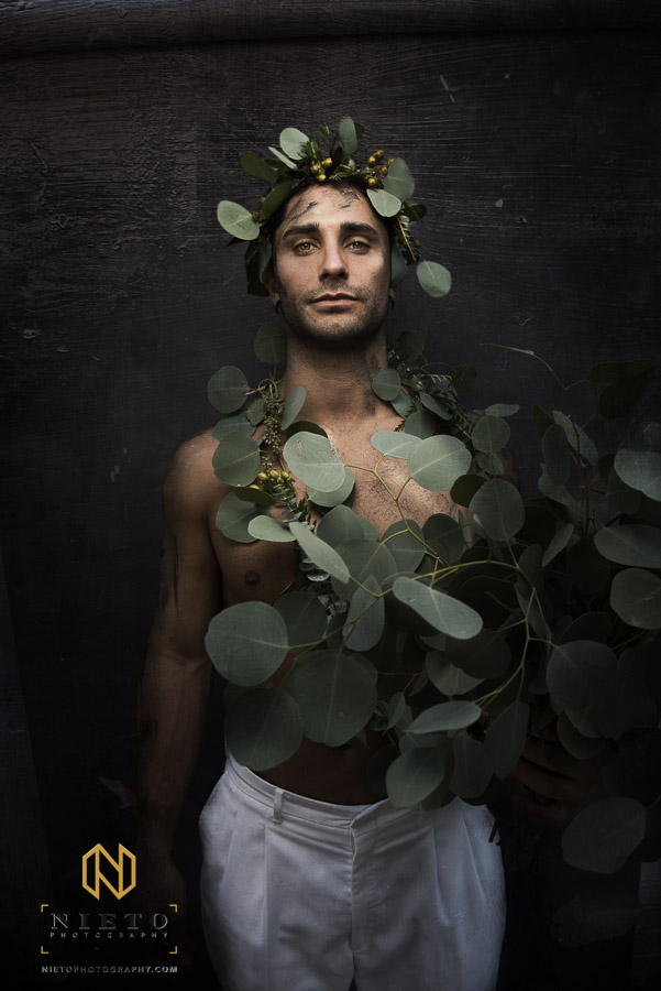 male model facing camera wrapped in greenery against textured wall