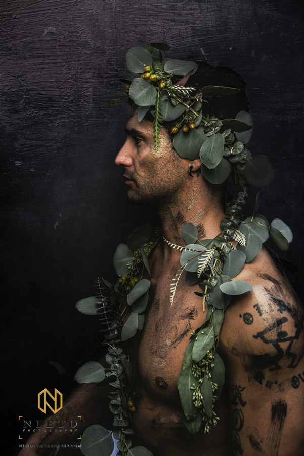 profile shot of male model wrapped in greenery and greenery crown