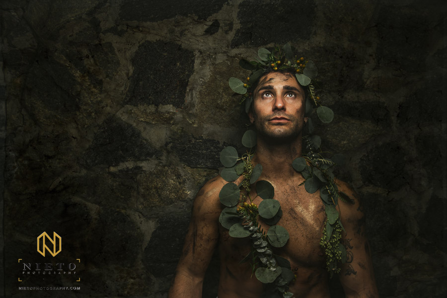 male model against stone wall with greenery around body