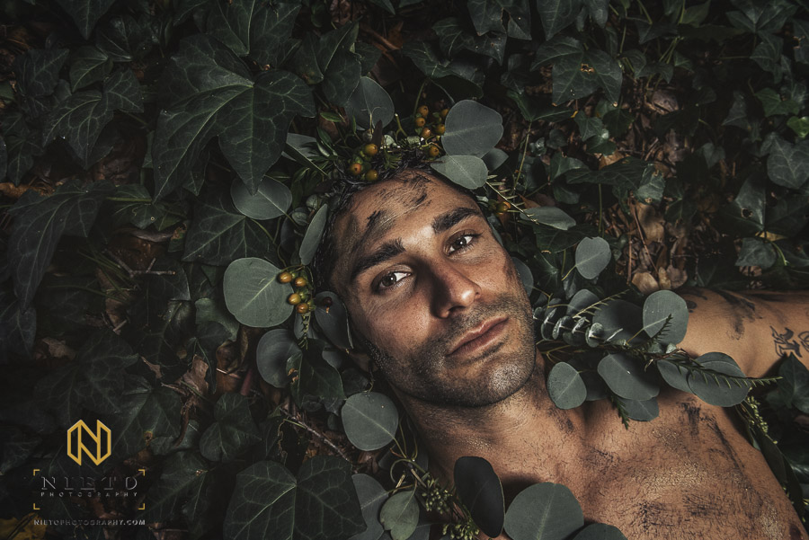male model laying in ivy with greenery crown