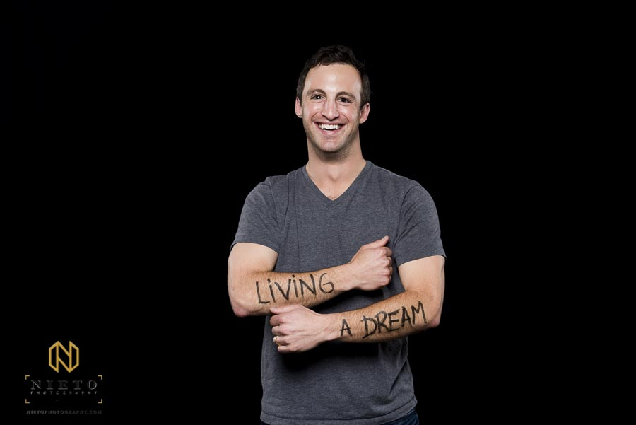 man posing for Duke Fuqua Reflects portrait with the words living a dream written on his arms