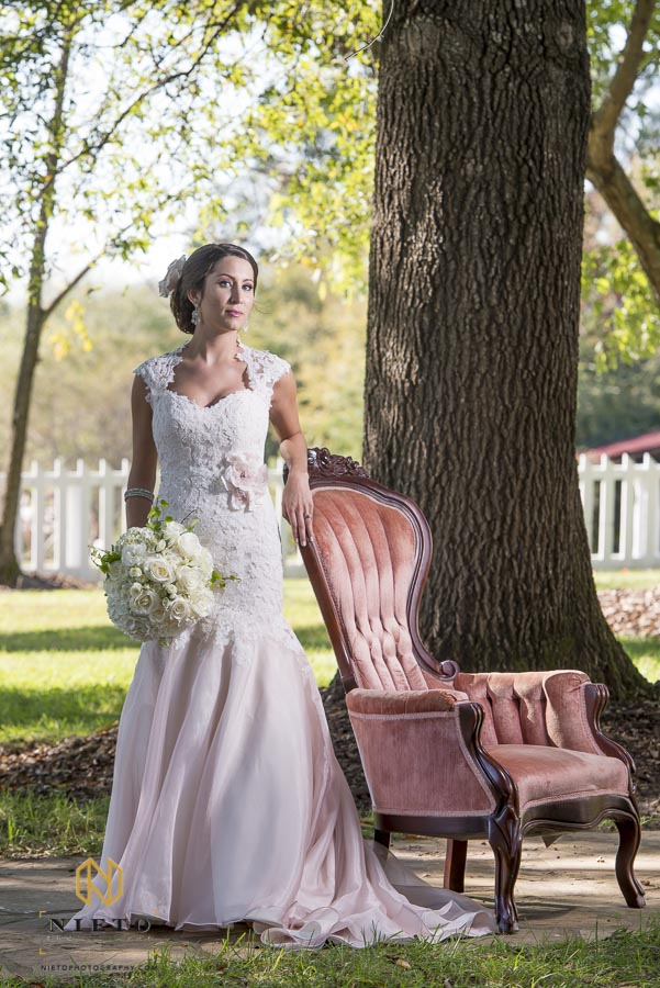 bride holding flowers while looking at camera and leaning on chair