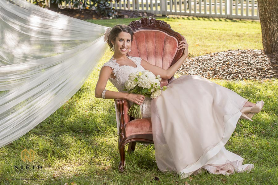 bride sitting back in chair with veil blowing in the wind