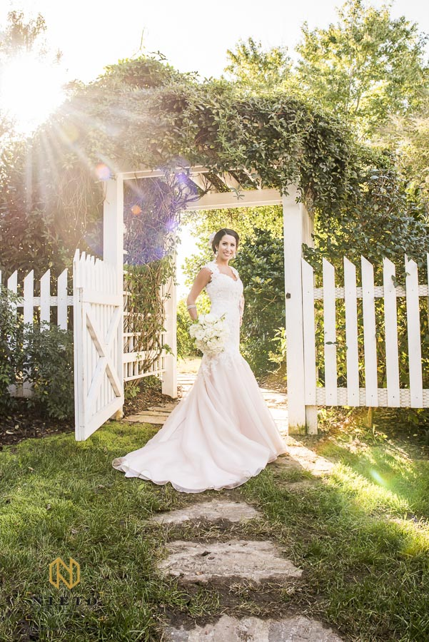 bride smiling under arbor at Lake o the woods
