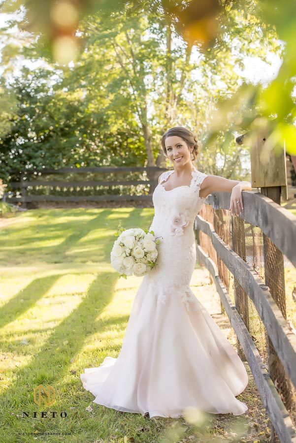 bride leaning against wooden fence on a fall day