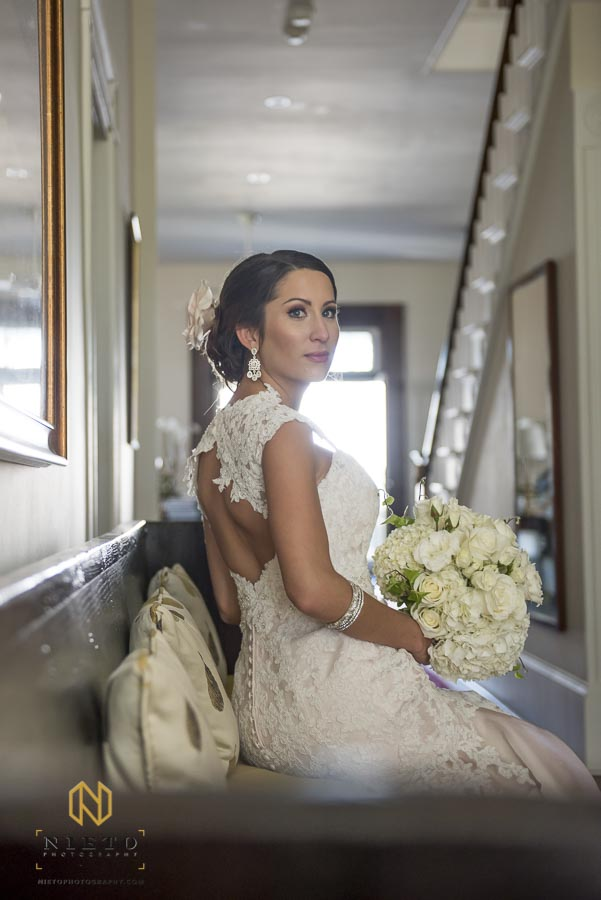 bride sitting in hall way holding her flowers at Lake O' the Woods