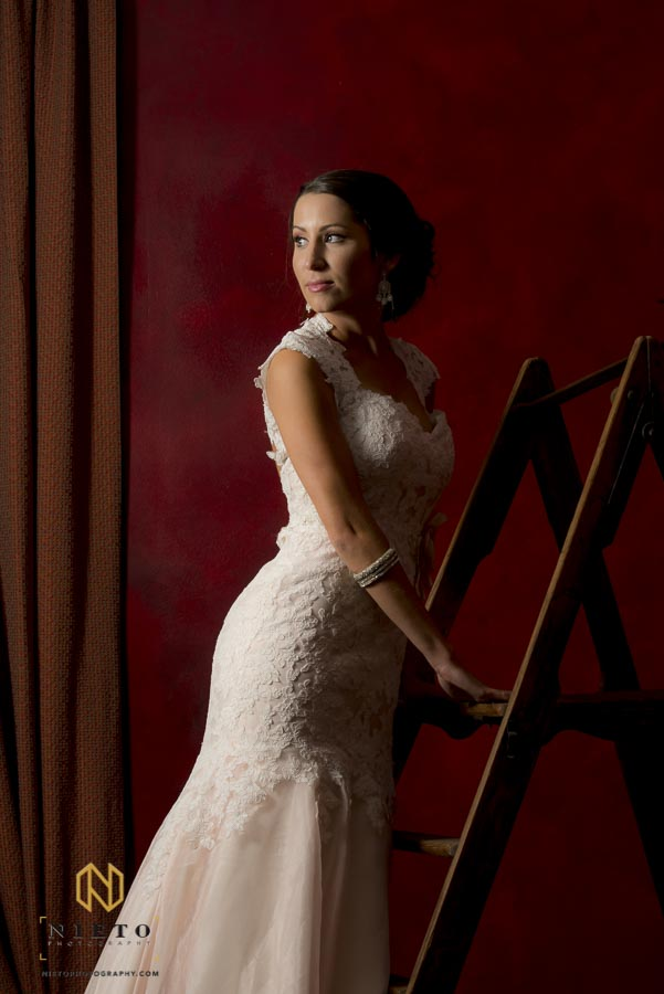 bride posing in the red room while standing on a ladder not looking at the camera
