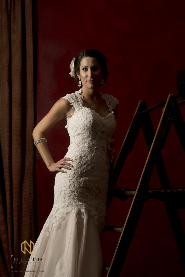 bride posing in the red room while standing on a ladder