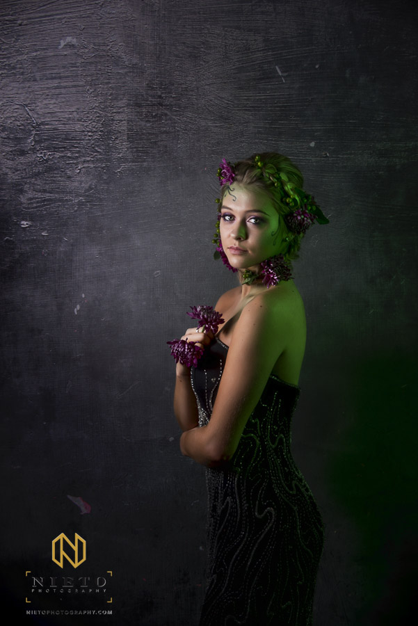 Model in black dress in green make up and purple flowers
