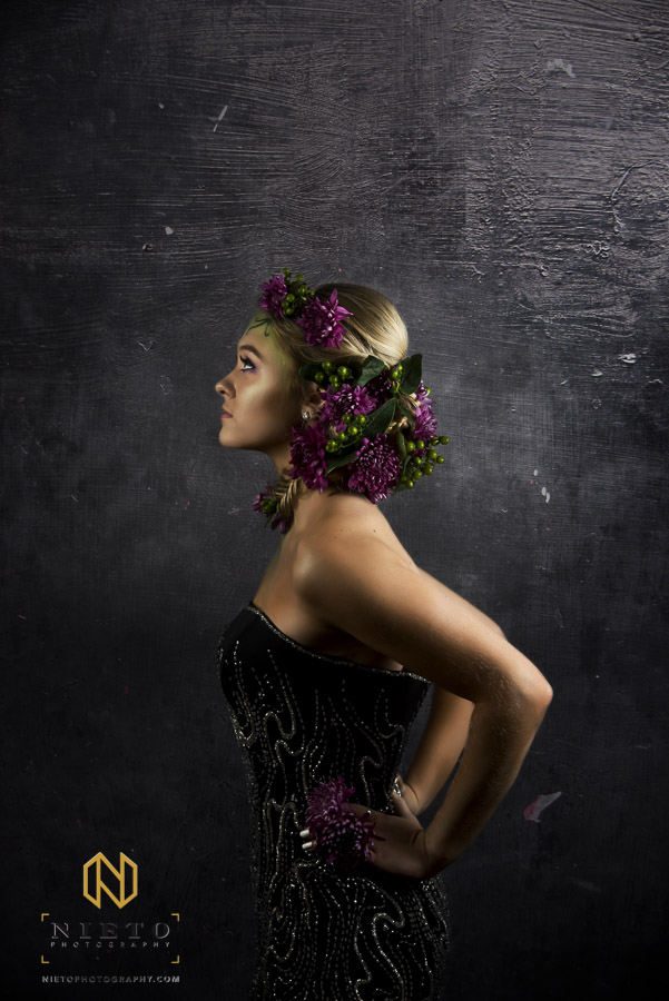 Model in black dress in green make up and purple flowers looking right