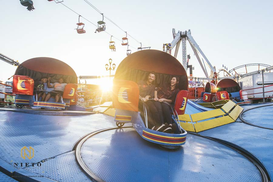 couple riding the tilt-a-whirl at sunset