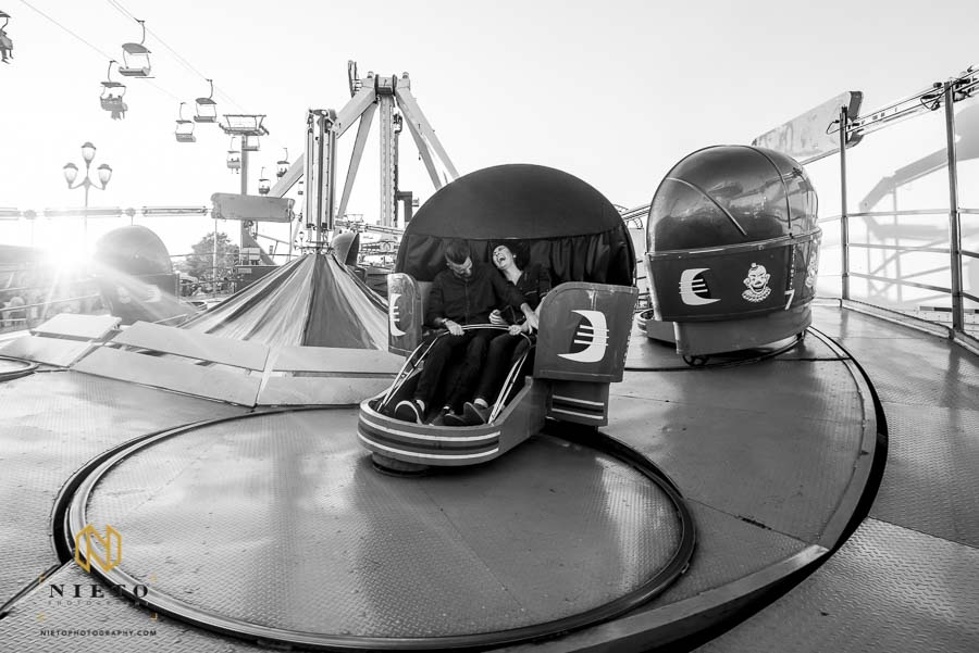 black and white picture of couple riding the tilt-a-whirl at the NC State Fair