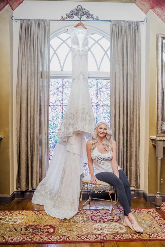 bride posing with her wedding gown while it hangs from a window in the bridal suite at Barclay Villa
