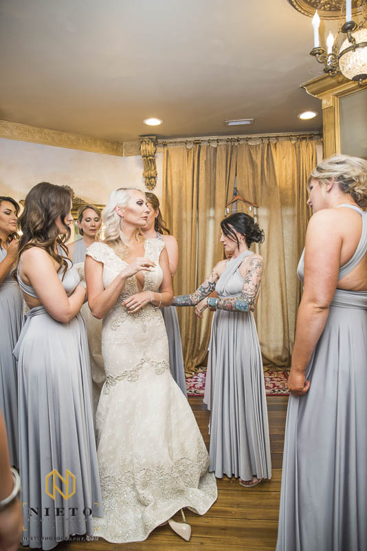 bride having her dress adjusted by her bridesmaids at Barclay Villa