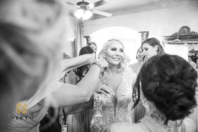 Black and white image of a bride smiling while her bridesmaids fix her dress and hair at Barclay Villa