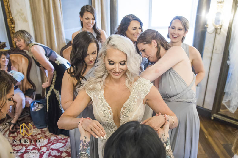 bride and bridesmaids smiling as they adjust the brides dress