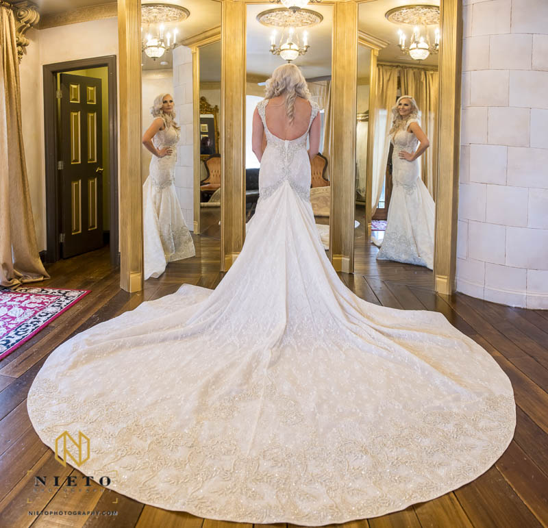Bride standing in front of three mirrors with her gown spread out behind her at Barclay Villa