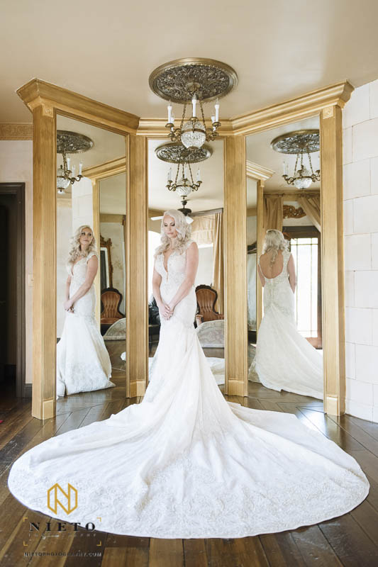 bride standing with her back to three mirrors as her reflection looks back at her