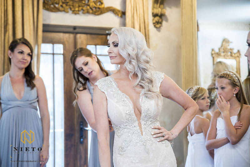 bride standing still as her bridesmaids help her fix the back of her gown