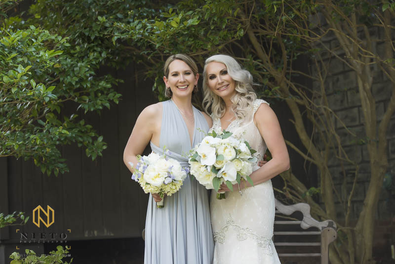 bride posing with her bridesmaid with their bouquets