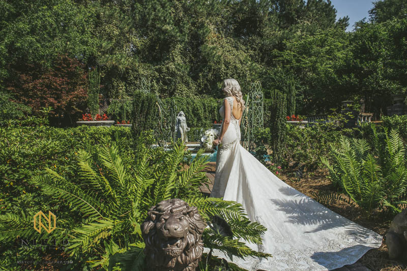 Bride standing in the garden at Barclay Villa with her gown trailing behind her