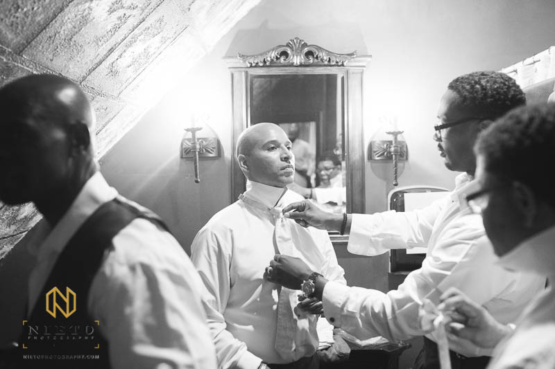 black and white image of a groomsman adjusting the grooms tie