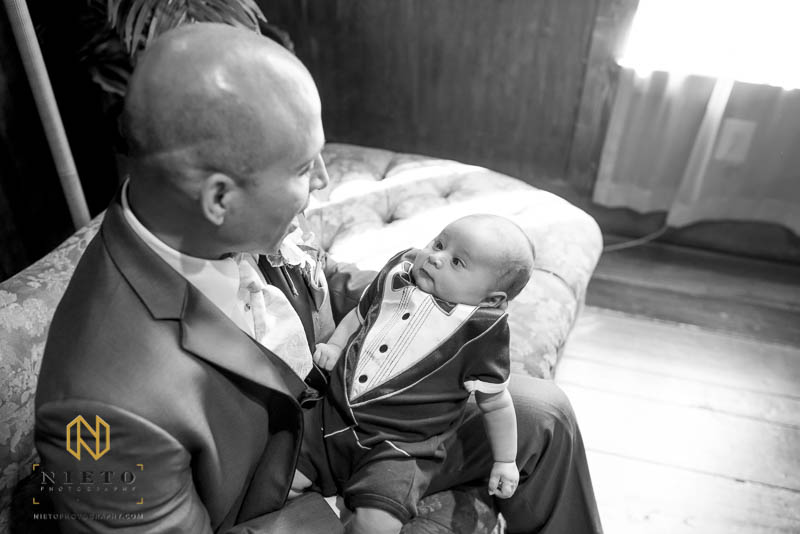 the groom talking to his infant son who is dressed in a Tux shirt