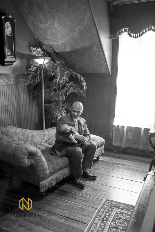 black and white image of the groom holding his sun in the game room of Barclay Villa