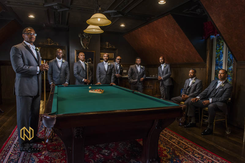 The groom and his groomsmen posing around the pool table at barclay villa