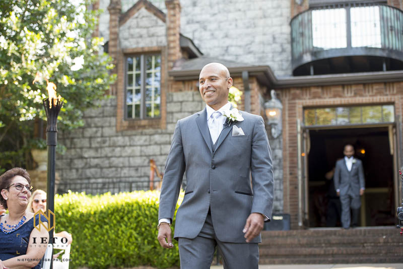 the groom smiling as he walks down the aisle at Barclay Villa