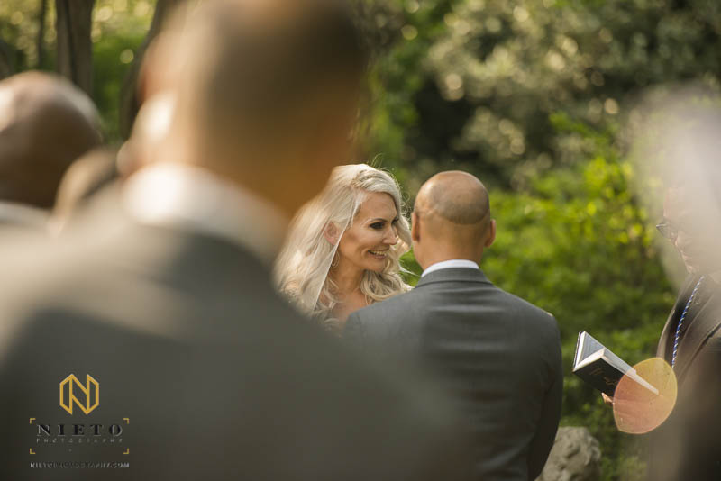 the bride smiling at the minister while she stands in front of the groom during her Barclay Villa wedding