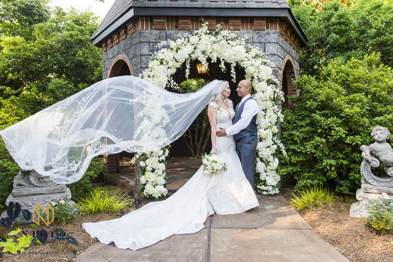 bride and groom standing in front of the floral arbor at Barclay Villa as her veil blows in the wind