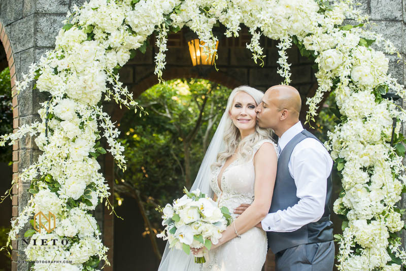 Groom kissing his bride on the cheek under the floral arbor at their Barclay Villa wedding