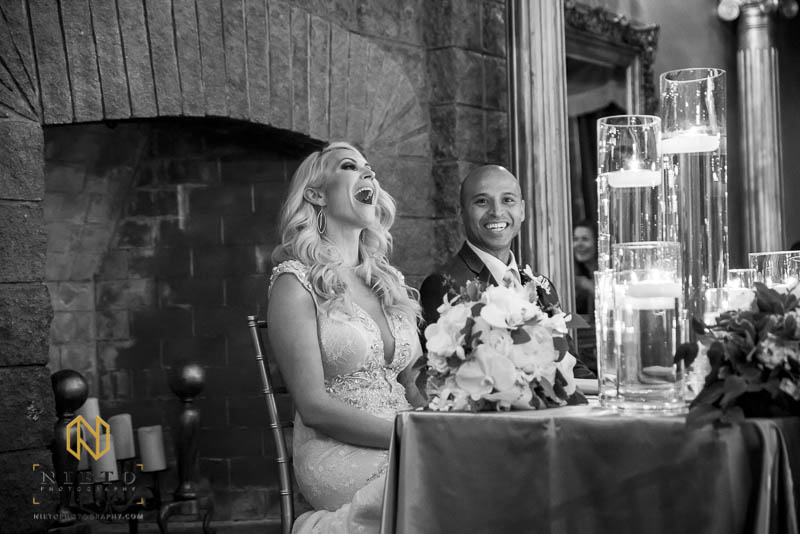 black and white picture of bride laughing out load as the groom smiles
