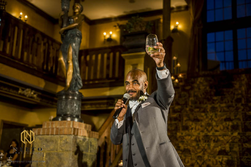 the best man holding up his glass to toast the bride and groom
