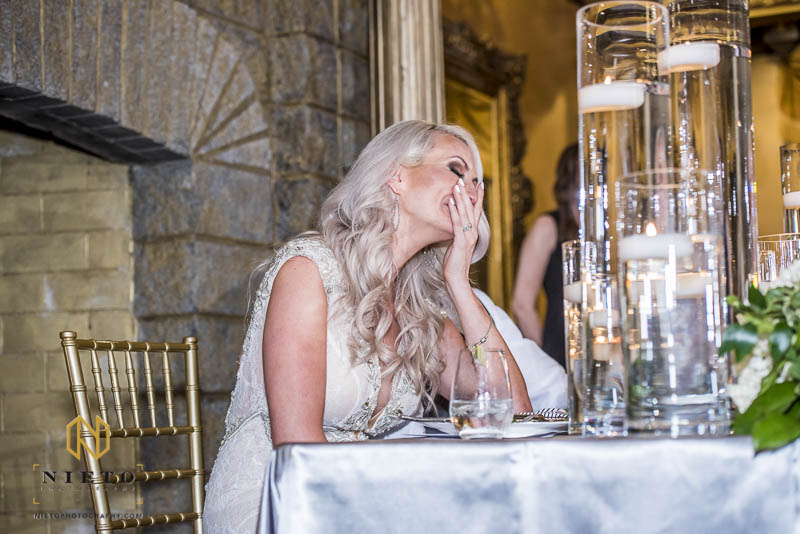 bride covering her face while laughing during her bridesmaids speech