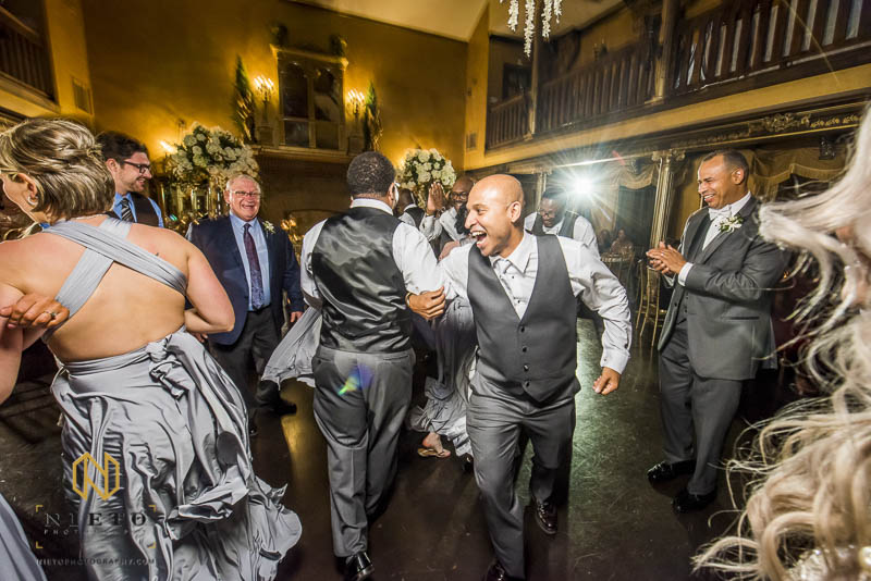 groom locking arms with a groomsman while dancing at Barclay Villa wedding
