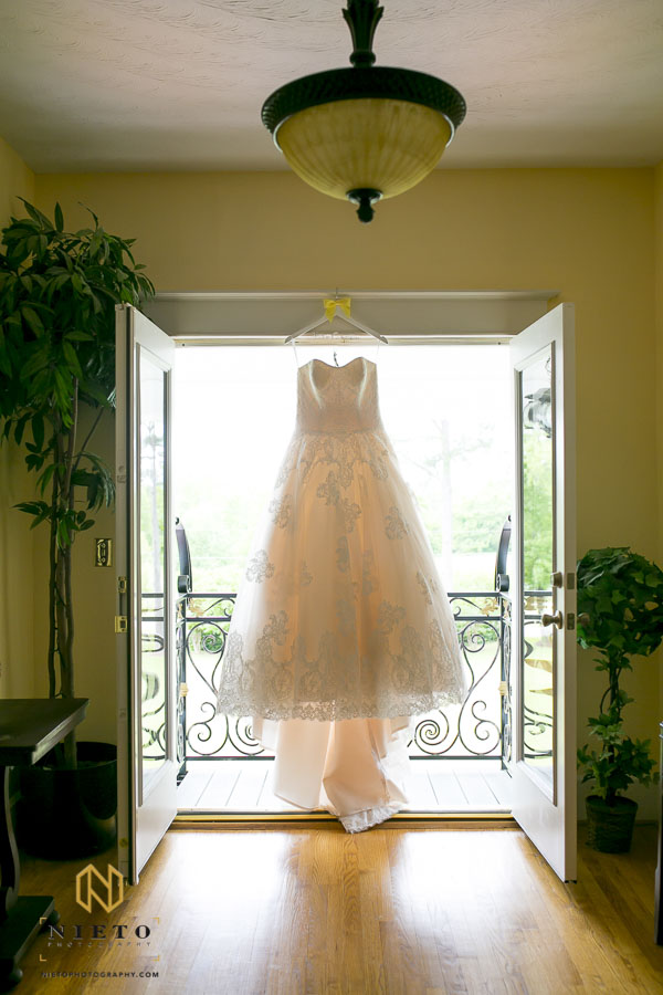 Brides wedding gown hanging from the french doors upstairs at the Hudson Manor