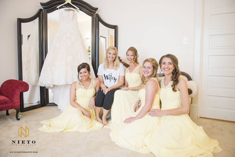 Bride sitting beside wedding gown with bridesmaids at the Hudson Manor