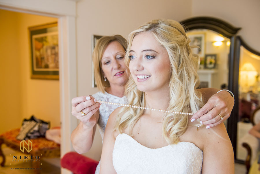 Bride having her pearl necklace placed by her mother