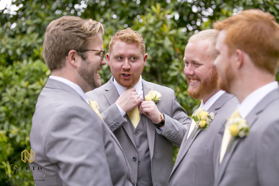 Groom showing groomsmen how to adjust their ties