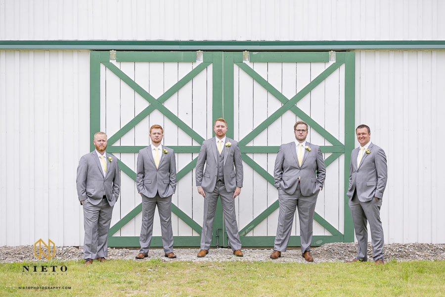 Groom and groomsmen standing in front of the horse stables at the Hudson Manor