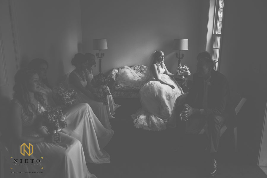 bride lit with window light as her father and bridesmaids sit in the shadows of the chapel at the Hudson Manor