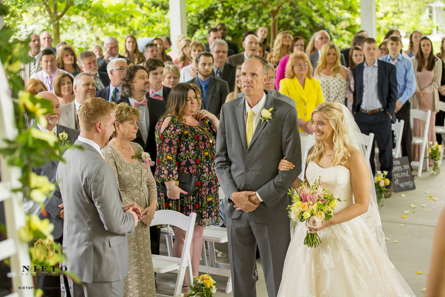 Bride smiling at the groom at the end of the isle while standing with her father at the Hudson Manor