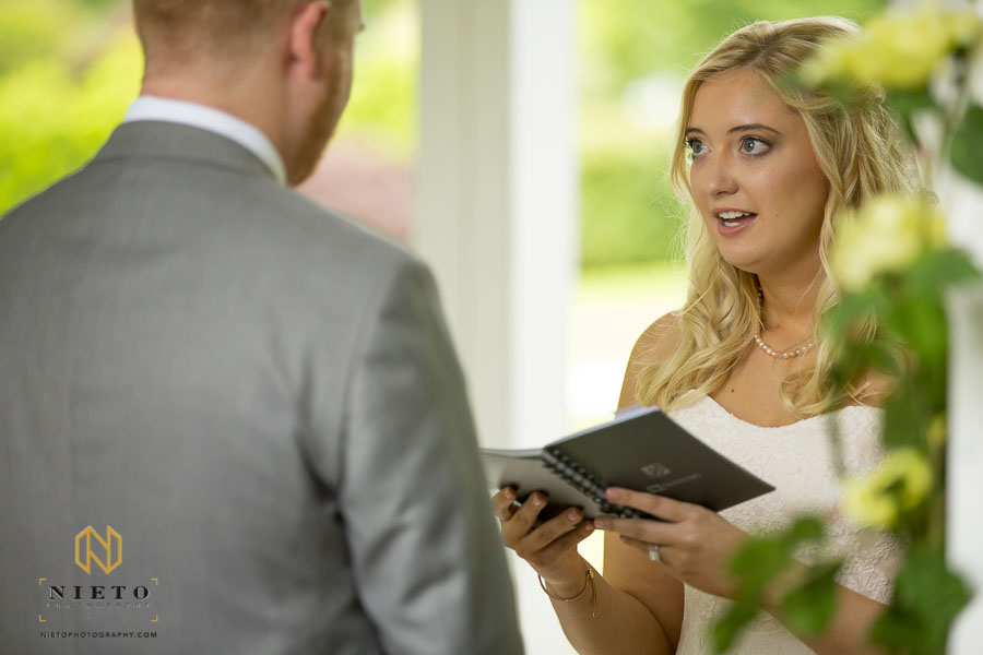 bride reading her vows from a small notebook to her groom at the Hudson Manor